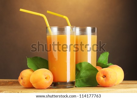 glasses of apricot juice on wooden table on brown background