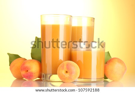 glasses of apricot juice on yellow background