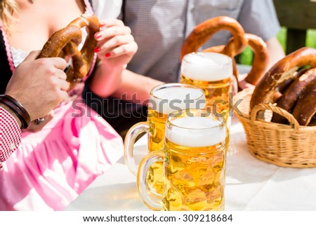 Glasses of beer and pretzel in German beer garden, close-up on the drinks and food - stock photo