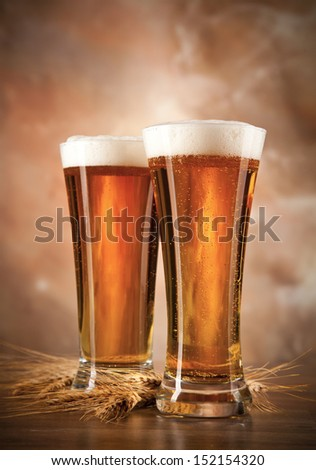 Glasses of beer on woden table