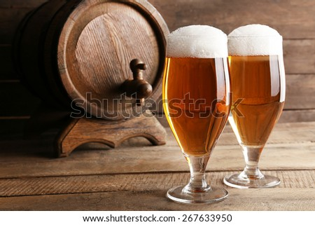Glasses of beer on wooden background - stock photo