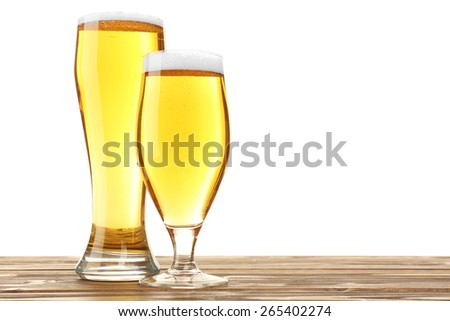 Glasses of beer on wooden table, isolated on white