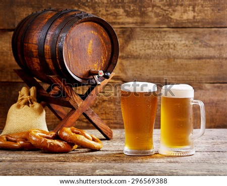 glasses of beer with barrel on wooden background - stock photo