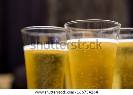 Glasses of beer with bubbles floating and on top - stock photo