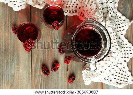Glasses of blackberry juice on wooden table, top view
