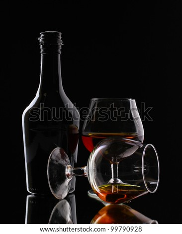 Glasses of brandy and bottle on black background