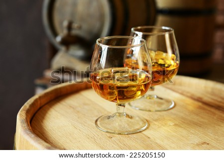 Glasses of brandy in cellar with old barrels  - stock photo