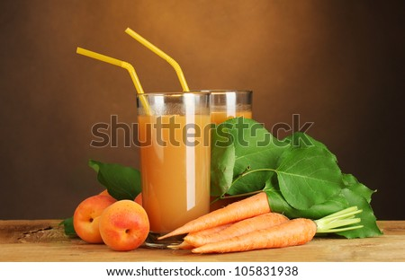 glasses of carrot and  apricot juice on wooden table on brown background - stock photo