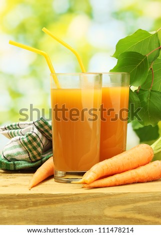 glasses of carrot juice and fresh carrots on wooden table on green background - stock photo