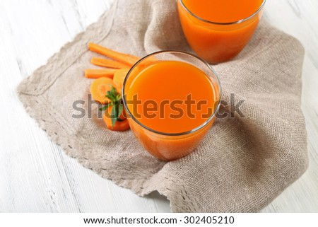 Glasses of carrot juice with vegetable slices on table close up