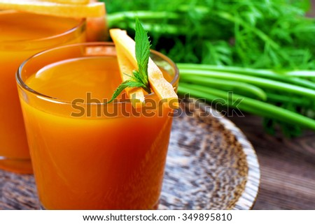 Glasses of carrot juice with vegetables on table close up - stock photo