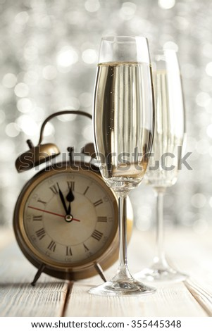 Glasses of champagne and alarm clock on wooden background