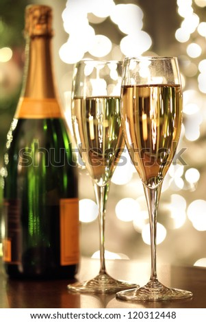 Glasses of champagne and bottle with festive background - stock photo