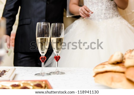 Glasses of champagne and bride and groom on background, selective focus - stock photo