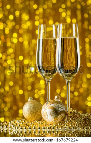 glasses of champagne and Christmas balls on a gold background