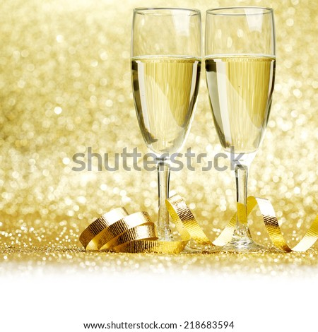 Glasses of champagne and curly decorative ribbon on golden glitters