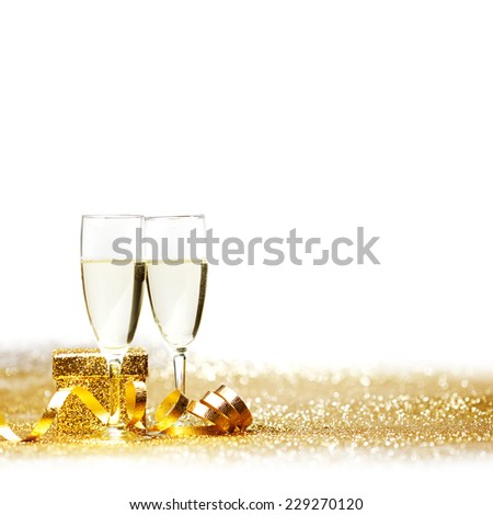 Glasses of champagne and decorative golden ribbon isolated on white - stock photo