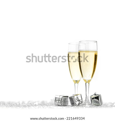 Glasses of champagne and silver gifts on glitter background - stock photo