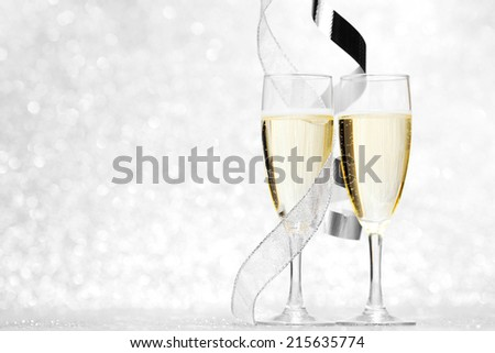 Glasses of champagne and silver ribbons on glitter background - stock photo