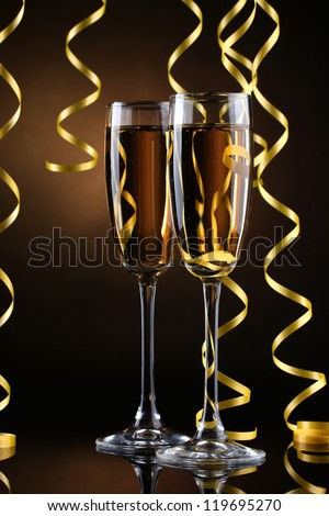 glasses of champagne and streamer on brown background - stock photo