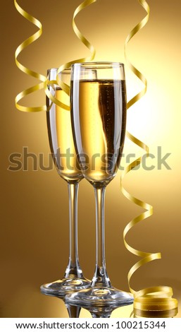 glasses of champagne and streamer on yellow background - stock photo
