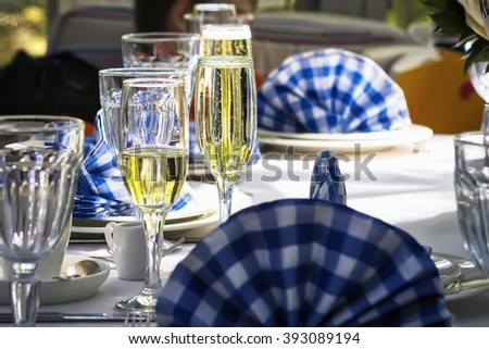 Glasses of champagne on festive decorated table with a white and blue napkins de-focused. - stock photo