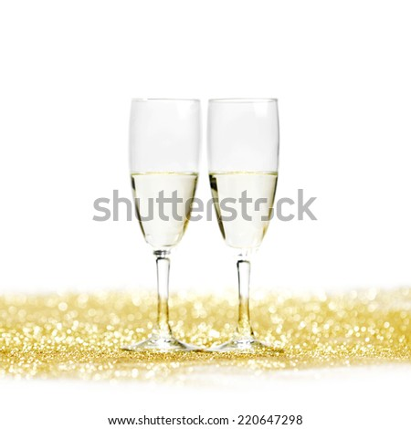Glasses of champagne on golden glitters isolated on white