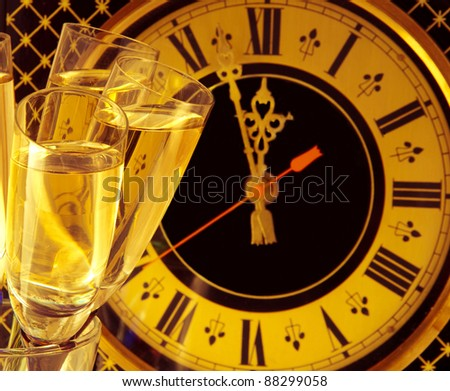 Glasses of champagne on New Year's Eve against an ancient wall clock - stock photo
