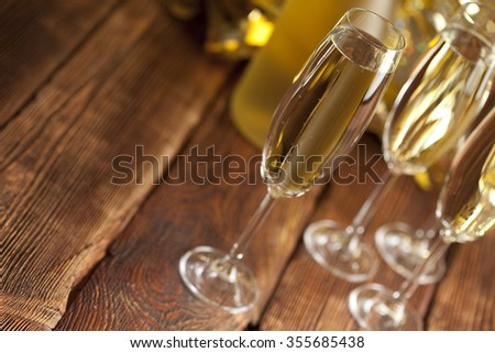 Glasses of champagne on wooden background - stock photo