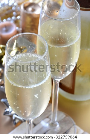glasses of champagne with bottle and New Year decoration - stock photo