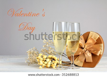 glasses of champagne with gift and herbarium on wooden table on grey background with inscription