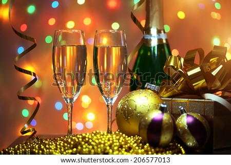 Glasses of champagne with gift box. background of lights