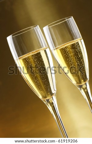 Glasses of champagne with gold background with walnuts, candels and dryed raisins - stock photo