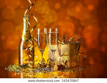Glasses of champagne with gold ribbon gift