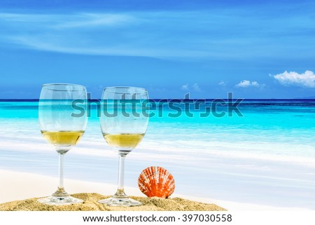 Glasses of champagne with  seashell on the beach against the sky and blue sea, add soft grain - stock photo