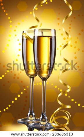 Glasses of champagne with serpentine on bright background - stock photo