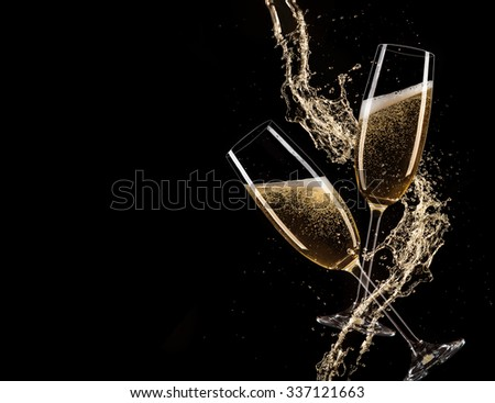 Glasses of champagne with splash, celebration theme.