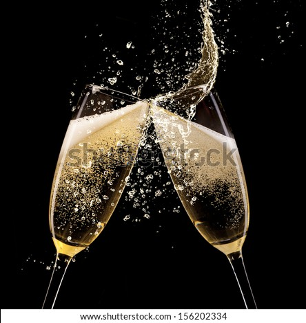 Glasses of champagne with splash, isolated on black - stock photo