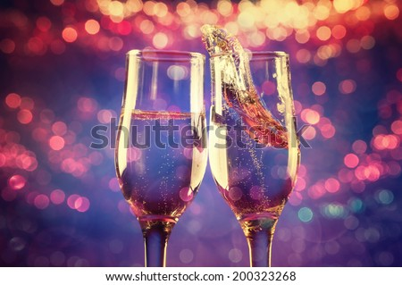 Glasses of champagne with splash on abstract background