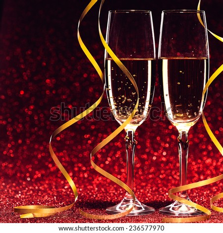 glasses of champagne with yellow holidays ribbons, on red background - stock photo