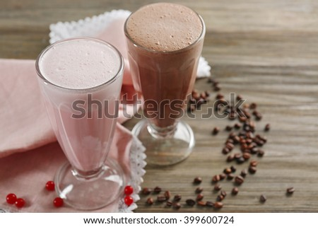 Glasses of chocolate and fruit milkshakes and coffee beans on wooden background - stock photo