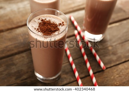 Glasses of chocolate milkshake on wooden table closeup - stock photo