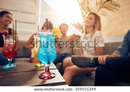 Glasses of cocktail on table with young people sitting on sofa on roof top. Friends having a rooftop party. - stock photo