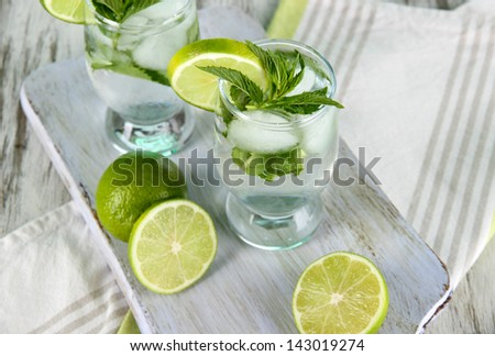 Glasses of cocktail with ice on board on napkin on wooden table