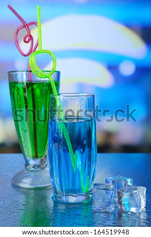 Glasses of cocktails, on bright background