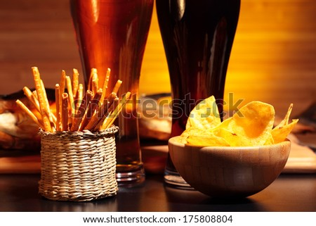 Glasses of dark and light beer with chips and snacks - stock photo