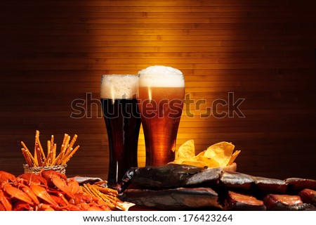 Glasses of dark and light beer with crawfish - stock photo