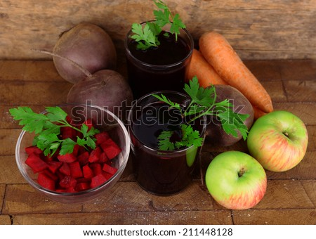 Glasses of fresh beet juice and vegetables on wooden background - stock photo