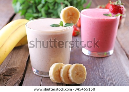 Glasses of fresh cold smoothie with fruit and berries, on wooden background - stock photo