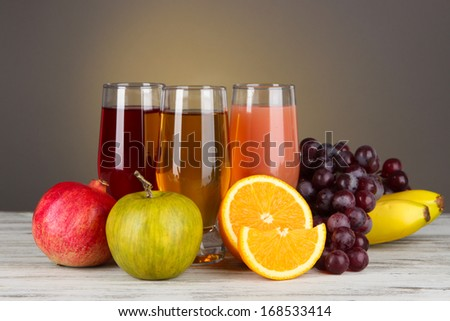 Glasses of fresh juice on table on gray background - stock photo